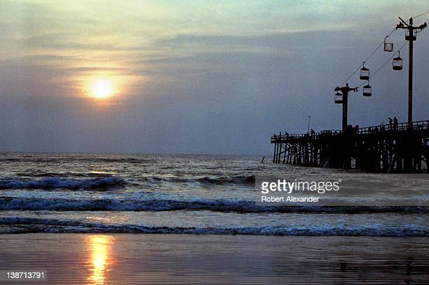 The sun rises above the Atlantic Ocean at Daytona Beach Florida as fishermen cast their lines from the Daytona Beach Pier