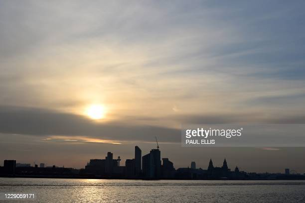 The sun rises across the River Mersey and the Liverpool skyline in north west England on October 14, 2020. - The government announced further...