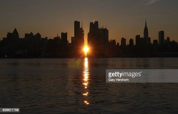 The sun rises along 42nd Street in New York City on January 16, 2017 as seen from Weehawken, NJ.