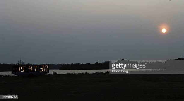 The sun rises as the Space Shuttle Endeavour sits on the launchpad in the far background behind the countdown clock Tuesday Aug 7 2007 The shuttle is...