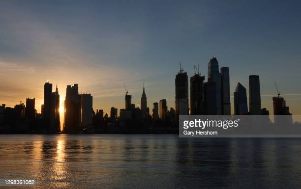 The sun rises behind 42nd Street, the Empire State Building and Hudson Yards in New York City on January 25, 2021 as seen from Weehawken, New Jersey.