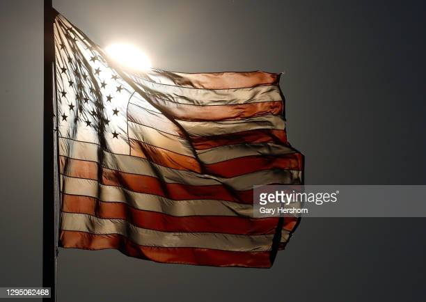 The sun rises behind a flag at Liberty State Park on January 7, 2021 in Jersey City, New Jersey.