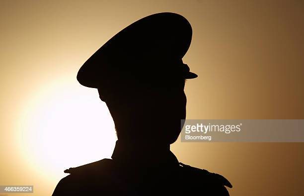 The sun rises behind a paramilitary police officer standing guard outside Tiananmen Square ahead of the closing session of the third session of the...