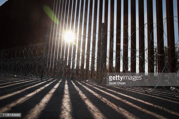 The sun rises behind a steel and concertina wire barrier that runs behind a shopping mall along the border of the United States and Mexico on January...