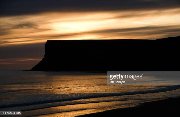 The sun rises behind clouds over Huntcliff cliffs on September 14 2019 in Saltburn By The Sea England Today the country will have sunshine for many...
