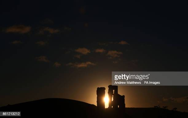 The sun rises behind Corfe Castle on the day of the Autumn Equinox in Dorset