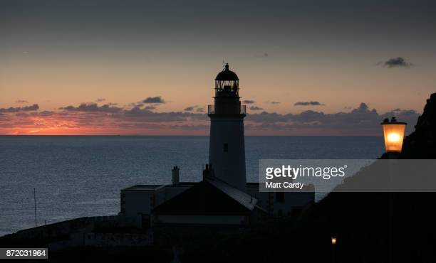 The sun rises behind Douglas Head lighthouse on November 7 2017 in Douglas Isle of Man The Isle of Man is a lowtax British Crown Dependency with a...