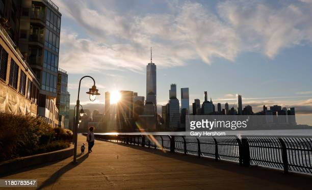 The sun rises behind lower Manhattan and One World Trade Center in New York City on October 13 2019 as seen from Jersey City New Jersey