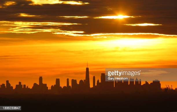 The sun rises behind lower Manhattan and One World Trade Center in New York City on August 20, 2021 as seen from Green Brook Township, New Jersey.