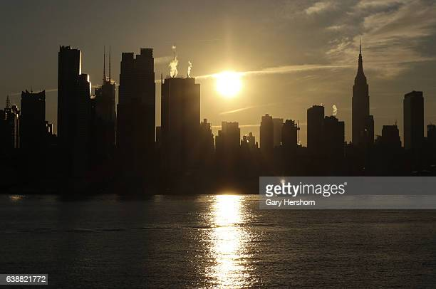 The sun rises behind midtown Manhattan and the Empire State Building in New York City on January 16, 2017 as seen from Weehawken, NJ.