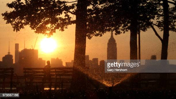 The sun rises behind midtown Manhattan and the Empire State Building in New York City on June 18 2018 as seen from Hoboken New Jersey