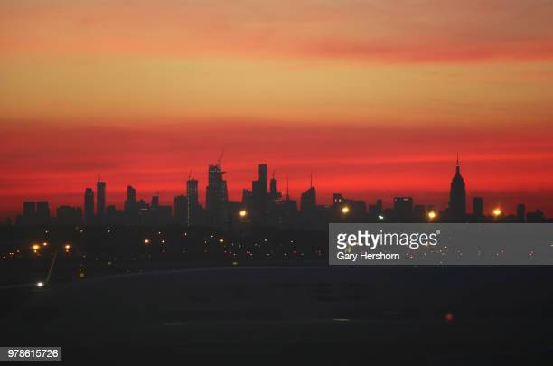 The sun rises behind midtown Manhattan in New York City on June 17 2018 as seen from Newark Liberty International Airport in Newark New Jersey