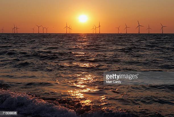 The sun rises behind one of the turbines which form Britain's largest offshore wind farm stand off the Great Yarmouth coastline on July 19 2006 in...