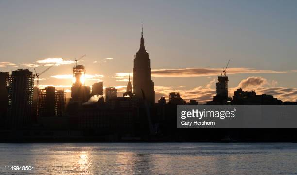The sun rises behind One Vanderbilt and the Empire State Building in New York City on May 15 2019 as seen from Hoboken New Jersey