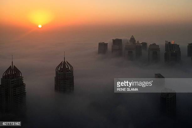 TOPSHOT The sun rises behind skyscrapers amidst the clouds on a foggy morning in Dubai on December 5 2016 / AFP / RENE SLAMA