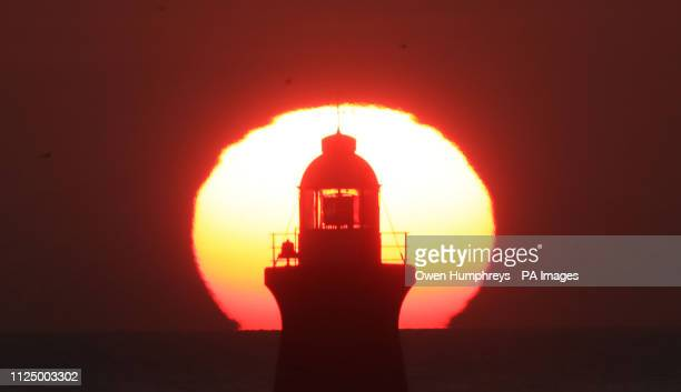 The sun rises behind South Shields Lighthouse on the River Tyne in North East. Forecasters have predicted another day of warm weather on Friday after...