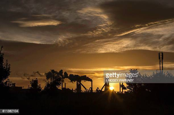 The sun rises behind the British Steel Scunthorpe plant in north Lincolnshire north east England on September 28 2016 Thursday September 29 marks 100...