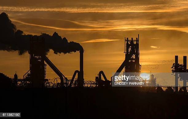 TOPSHOT The sun rises behind the British Steel Scunthorpe plant in north Lincolnshire north east England on September 28 2016 Thursday September 29...