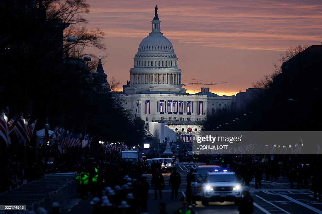 TOPSHOT - The sun rises behind the Capitol before the start of the US Presidential Inauguration of Donald Trump on January 20, 2017 in Washington, DC. Donald Trump will be sworn in as the 45th president of the United States Friday -- capping his improbable journey to the White House and beginning a four-year term that promises to shake up Washington and the world. / AFP / Joshua LOTT