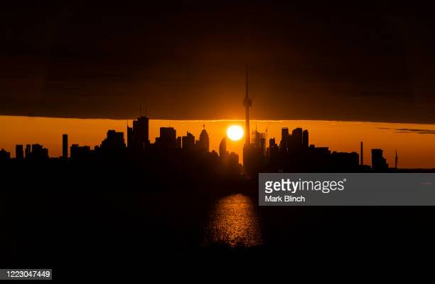 The sun rises behind the CN Tower and skyline on April 23 2020 in Toronto Canada