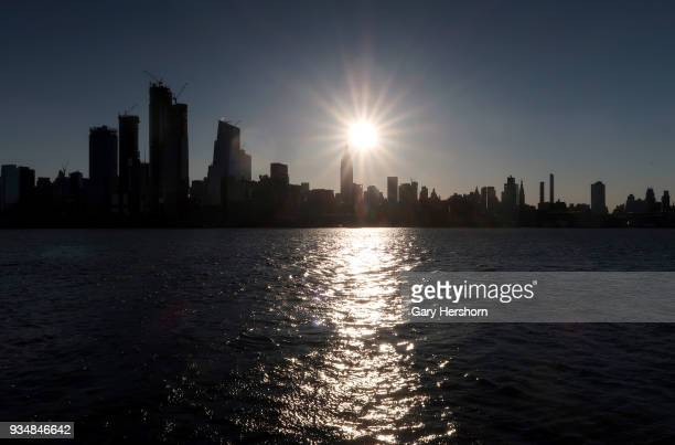 The sun rises behind the Empire State Building and Hudson Yards in New York City on March 18 2018 as seen from Hoboken New Jersey