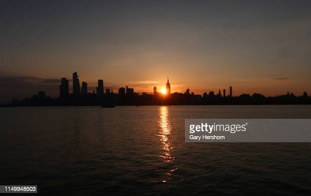 The sun rises behind the Empire State Building and One Vanderbilt and Hudson Yards in New York City on May 17 2019 as seen from Hoboken New Jersey