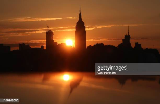 The sun rises behind the Empire State Building and One Vanderbilt in New York City on May 17 2019 as seen from Hoboken New Jersey