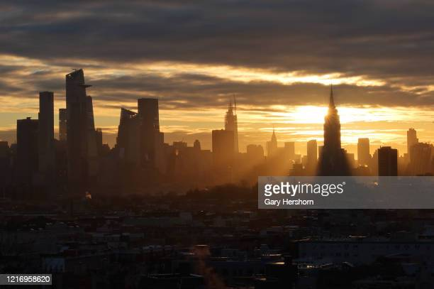 The sun rises behind the Empire State Building and the skyline of midtown Manhattan in New York City on April 5 2020 as seen from Jersey City New...