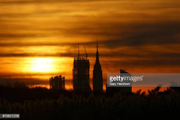 The sun rises behind the Empire State Building and the under construction 30 Hudson Yards in New York City on November 4 as seen from Lyndhurst New...