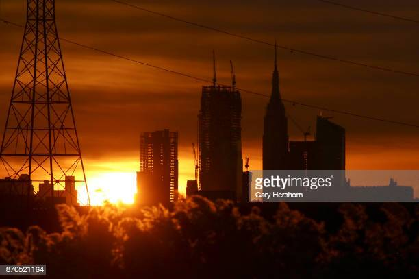The sun rises behind the Empire State Building and the under construction Hudson Yards in New York City on November 4 as seen from Lyndhurst New...
