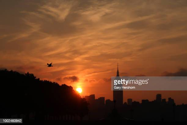 The sun rises behind the Empire State Building in New York City on July 17 2018 as seen from Hoboken New Jersey