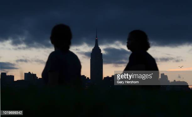 The sun rises behind the Empire State Building in New York City on August 15 2018 as seen from Hoboken New Jersey