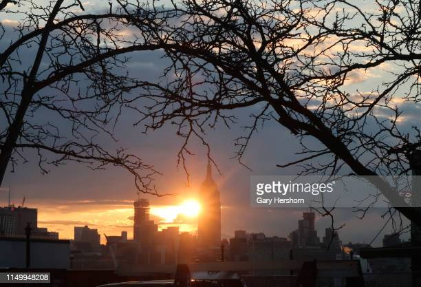 The sun rises behind the Empire State Building in New York City on May 16 2019 as seen from Hoboken New Jersey
