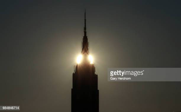 The sun rises behind the Empire State Building in New York City on March 18 2018 as seen from Hoboken New Jersey