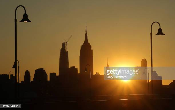 The sun rises behind the Empire State Building, One Vanderbilt and the Chrysler Building in New York City on May 31, 2020 as seen from Jersey City,...