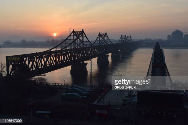 The sun rises behind the Friendship Bridge which spans the Yalu River between China and North Korea as seen from the Chinese city of Dandong in...