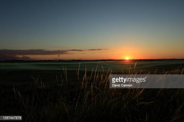 The sun rises behind the green on the par 4 18th hole at The Royal St George's Golf Club on July 20 2020 in Sandwich England