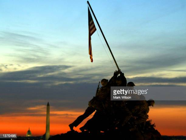 The sun rises behind the Iwo Jima Memorial the Washington Monument and the US Capitol September 6 2002 in Arlington Virginia