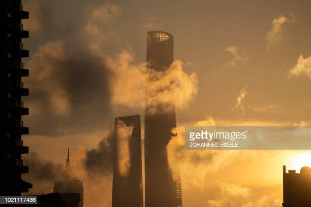 The sun rises behind the Jin Mao Tower Shanghai World Financial Center and the Shanghai Tower in the financial district of Pudong in Shanghai on...