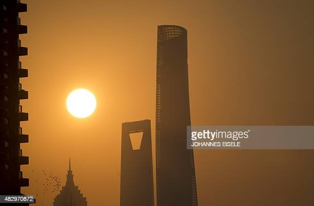 The sun rises behind the Jinmao Tower the Shanghai World Financial Center and the Shanghai Tower still under construction in Shanghai on August 5...