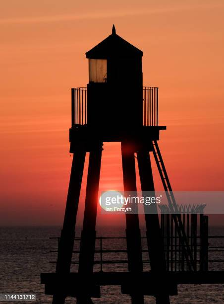 The sun rises behind the navigation beacon on Whitby East Cliff on Easter Sunday on April 21 2019 in Whitby United Kingdom Easter weekend weather has...