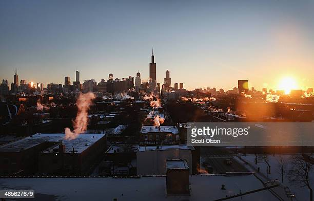 The sun rises behind the skyline as temperatures hovered around 10 degrees January 28 2014 in Chicago Illinois The city has had 18 days at or below...