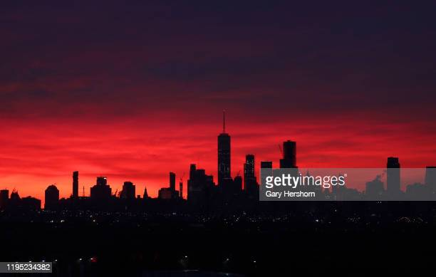 The sun rises behind the skyline of lower Manhattan and One World Trade Center on the winter solstice in New York City on Demember 21, 2019 as seen...