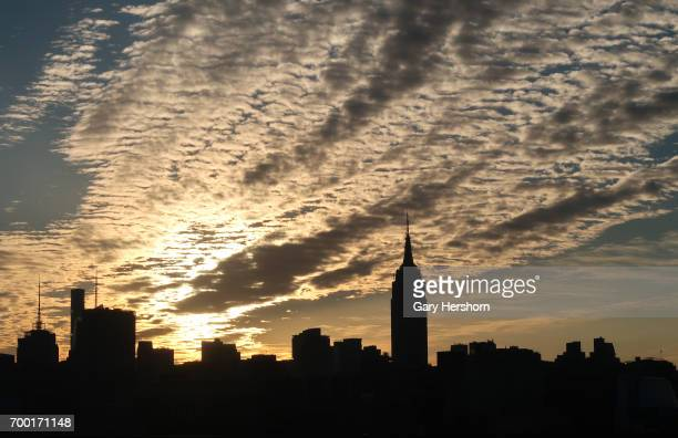 The sun rises behind the skyline of midtown Manhattan and the Empire State Building on the summer solstice in New York City on June 21 2017 as seen...