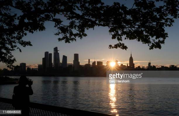 The sun rises behind the skyline of midtown Manhattan Hudson Yards and the Empire State Building in New York City on May 15 2019 as seen from Hoboken...