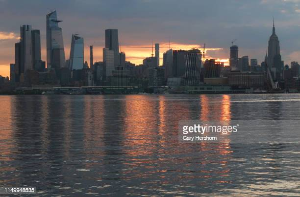 The sun rises behind the skyline of midtown Manhattan Hudson Yards and the Empire State Building in New York City on May 16 2019 as seen from Hoboken...