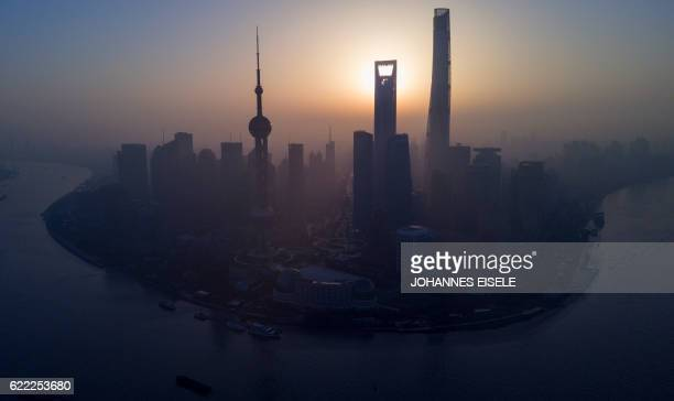 The sun rises behind the skyline of Shanghai in the Lujiazui Financial District of Pudong on November 11 2016 / AFP / JOHANNES EISELE