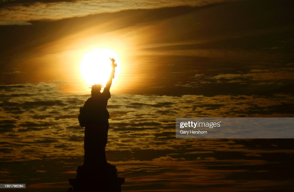 Sunrise Behind the Statue of Liberty in New York City : News Photo