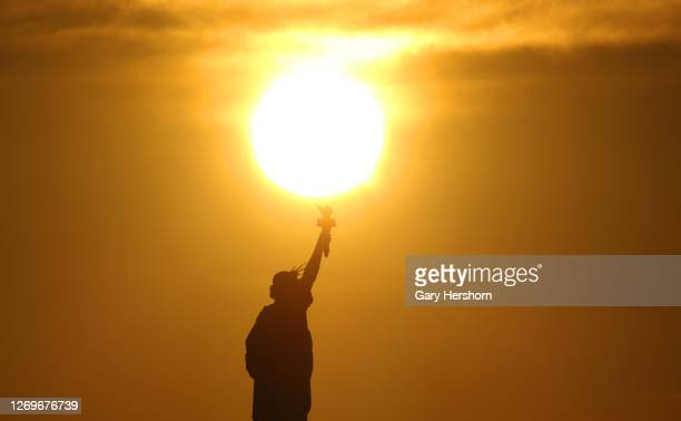 The sun rises behind the Statue of Liberty in New York City on August 30, 2020 as seen from Jersey City, New Jersey.
