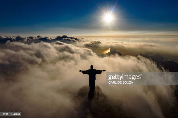 The sun rises in front of the Christ the Redeemer statue in Rio de Janeiro on March 24, 2021. - Christ the Redeemer is celebrating its 90th...